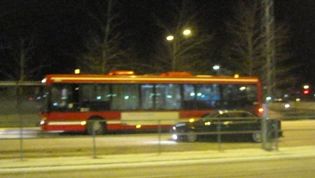 Bil som sladdar runt bland bussar och resenärer