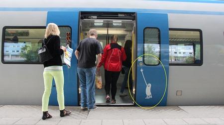 Rolig SL-gubbe visar var man skall trycka på knapp för att öppna dörren