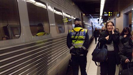 Polis från gränsskyddet kontrollerar tågresenärer ( Kvinnan på bilden har inget med kontrollen att göta )